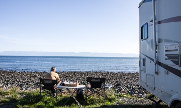 Ross is sitting, looking a the ocean, while their RV is parked at the small hamlet of Jordan River on Vancouver Island's west coast.
