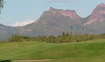 Golf green with mountains in background