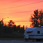 RV parked in a campsite with sunset in background