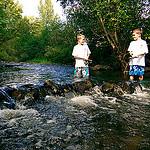 two boys fishing in a creek