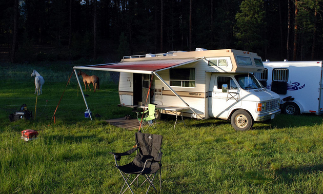 RV set up with a chair in front and two horses in the nearby pasture.