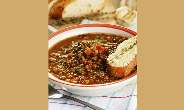 A bowl of hearty looking lentil stew is accompanied by a slice of french loaf and a spring of rosemary.