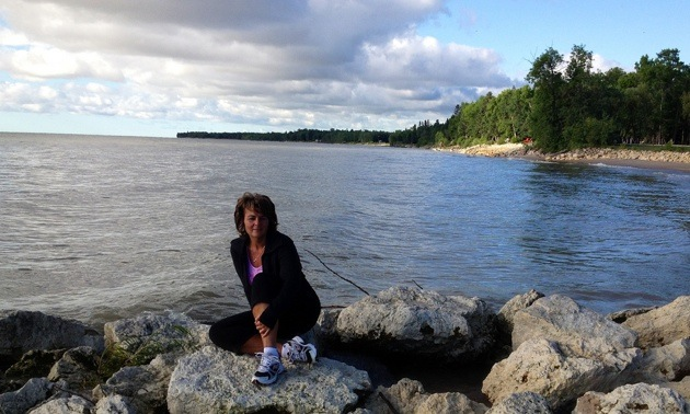 Photo of Laurie Oughton sitting on the rocks in front of a lake.