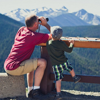 A father and sun looking through binoculars at a lookout at Manning Park.
