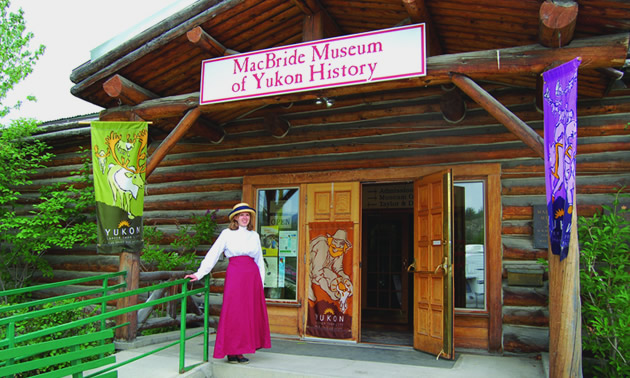 A woman dressed in a long red skirt and white blouse and hat stands in front of the MacBride Museum of Yukon History, ready to welcome visitors.