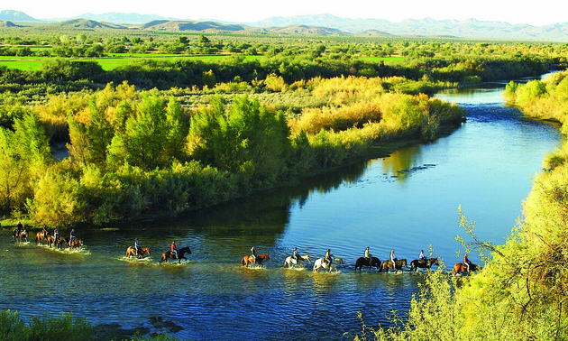 people on horseback riding through a river