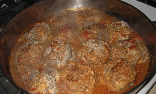 Meatballs simmering in a tomato sauce.
