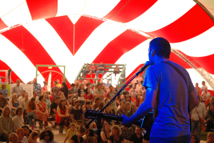 Musician plays in front of crowd under a tent