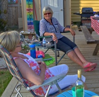 3 friends sitting in lawn chairs on a deck in front of an RV.