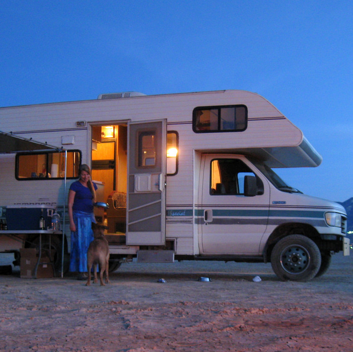 RV at an RV park with a smiling lady and her dog standing in front