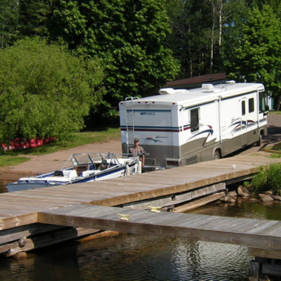 Picture of RV backing boat down a boat ramp.