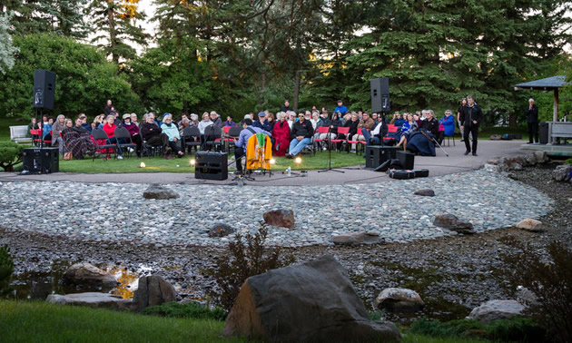 A group of people listening to a jazz player in the Japanese gardens in Lethbridge.