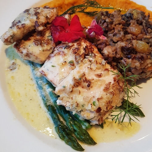 a fish dish with asparagus and other veggies on the side