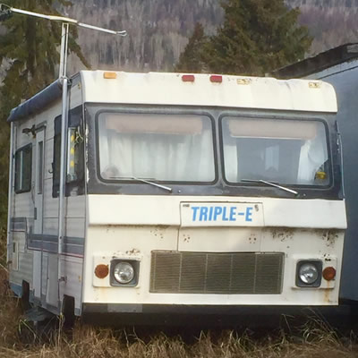 An old Triple E motorhome parked in tall grass.