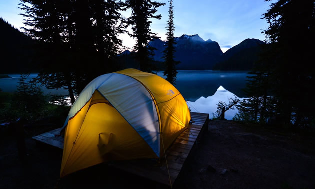 Picture of tent set up on lakeshore with mountains in the background.
