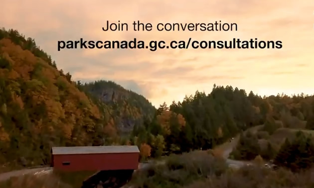 Video still from Parks Canada website, showing covered bridge and forest.