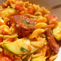 Saucy pasta is attractively arranged in a white bowl with pieces of chorizo, zucchini, and herbs.