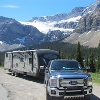 The Rogoza family's RV and truck on a road with snowcapped mountains in the background.