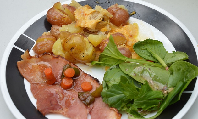 The plated meal of ham with apricot ginger glaze, potatoes with cheese and a fresh green salad.