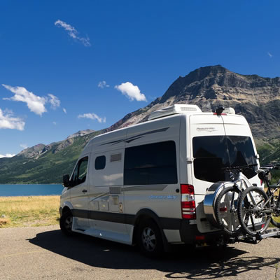A Pleasure-Way van, parked in front of a lake.
