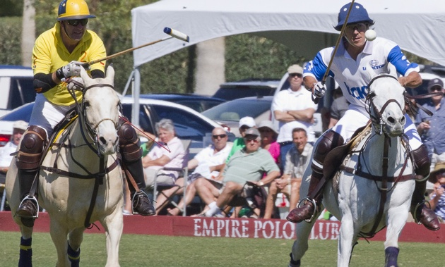 2 riders, one in yellow, the other in blue, playing polo at the Empire Polo Club in Indio, California.