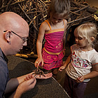 two kids with an adult showing them a tarantula spider at the Exploration Place