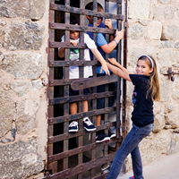 Children pretending to be locked into an old prison
