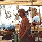 man standing behind a counter selling crafts at the Quartzsite show