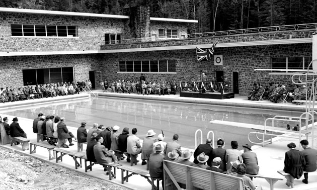 Many people are sitting and watching the opening ceremony of the Radium Hotsprings Aquacourt in Kootenay National Park.