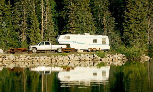 Overlooking a lake to see a truck and 5th wheel, parked in a campspot.
