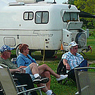 people sitting on lawn chairs beside RVs