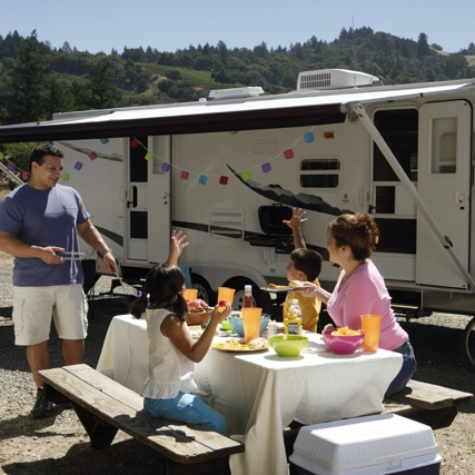 A family eating at a picnic table in front of their RV