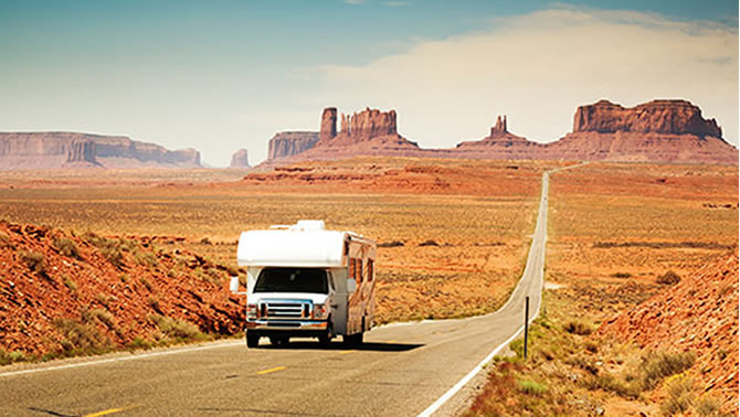 Picture of RV travelling down desert road.