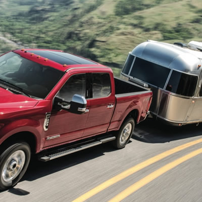 Picture of red Ford truck towing silver Airstream trailer.