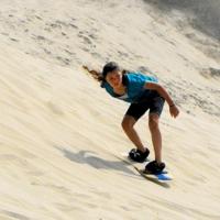 A young women sandboarding.