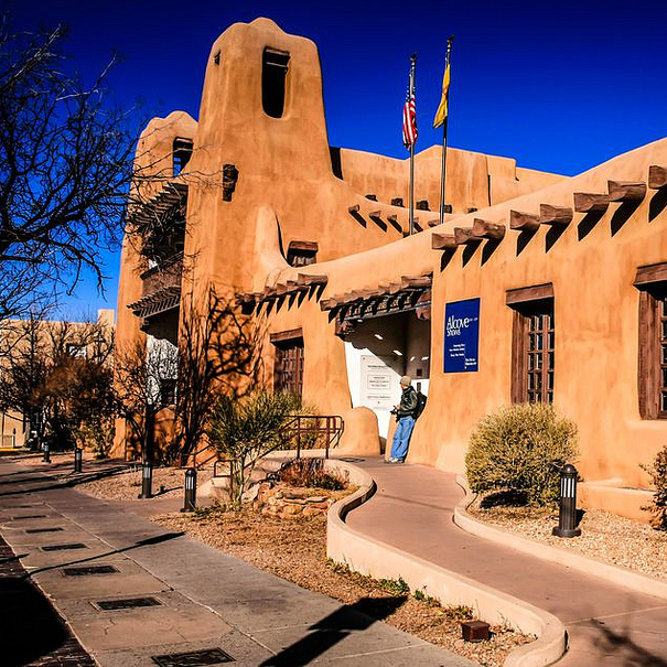 An adobe building in Santa Fe is silhouetted against a brilliant blue sky.