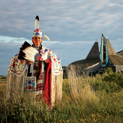 A First Nations woman in traditional garb stands outside the Wanuskewin Heritage Park.