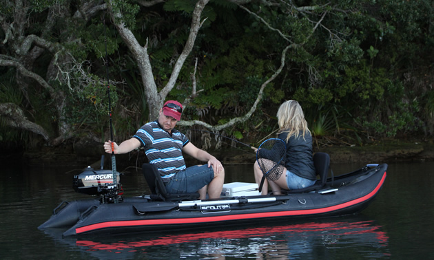 Picture of Scout boat in water, with two people sitting in boat.