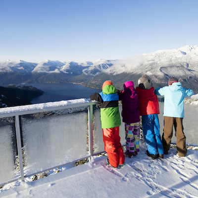 A group of kids standing at summit of mountain looking at view.