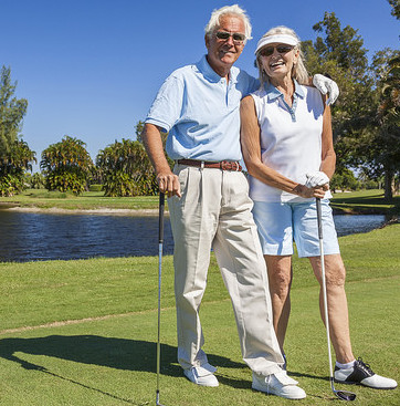 A happy senior couple standing with their clubs on a golf green.