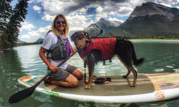 Christine Newmanis kneeling on a paddleboard with a shelter dog, Vincent (a Rottweiler-hound mix).