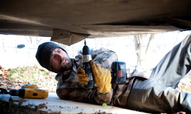 James Bryen replaces metal panelling underneath the Silver Streak after repairing a plumbing leak.
