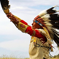 Elderly First Nations man in feather headdress and beaded leather clothing