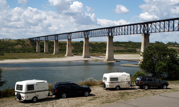 Campers parked by the river looking out toward the SkyTrail Bridge.