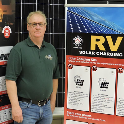 The author is standing in front of an RV solar power display.