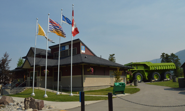 Shown is the front entrance of the Sparwood Chamber of Commerce with the Titan truck beside it.