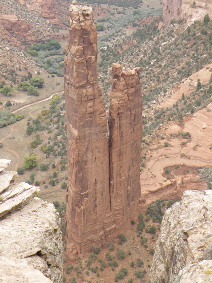 Two narrow rocks tower over a desert landscape
