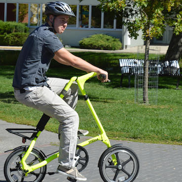 Spencer Shellborn riding a Strida Bike in a park.