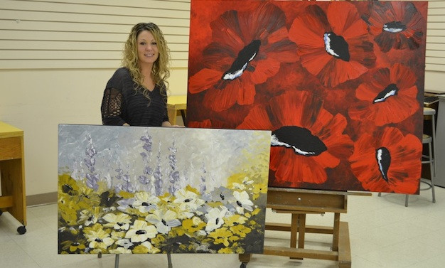 Camrose artist Tara Szott with her enormous floral canvases.