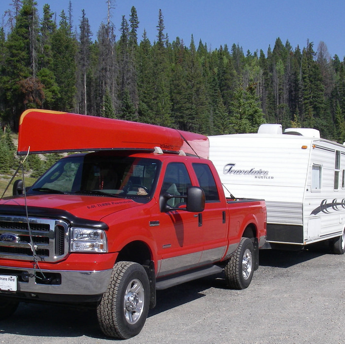 This photo shows the author's first RV, a trailer, being pulled by a red pick-up truck.